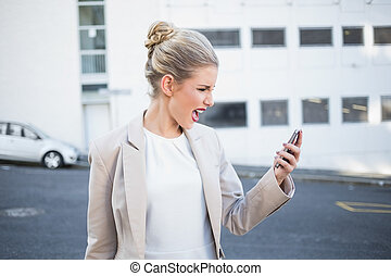 Furious stylish businesswoman shouting at her phone outdoors...
