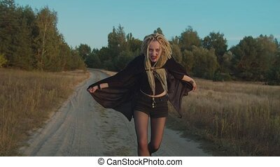 Portrait of spooky furious woman vampire with dreadlocks and bloody face in black cloak hissing and frightening on dirt road in rays of setting sun, expressing danger, horror and hunger for blood.