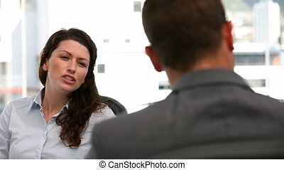 Furious woman during an interview with a man in her office