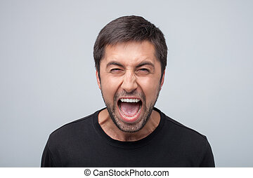 Furious young man is evincing negative emotions