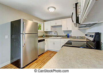 Furnished kitchen room with white cabinets and steel appliances
