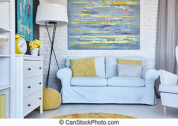 Cozy furnished living room with big painting on a wall