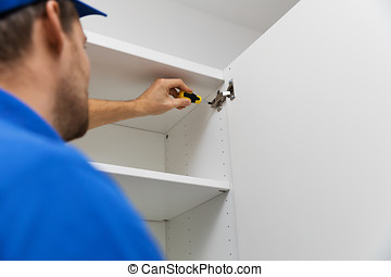 furniture assembly service - worker installing cabinet doors