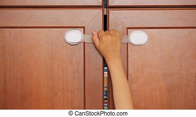 Furniture safety lock and child's hand on it
