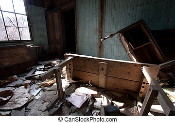 Old furniture that is turned upside down in a room full of trash.