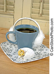 furry ear muffs on coffee cup - White furry ear muffs on a...