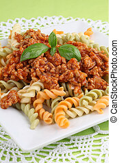 Colorful fusilli pasta with bolognese sauce and basil
