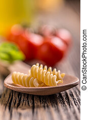 Fusilli pasta on wooden spoon