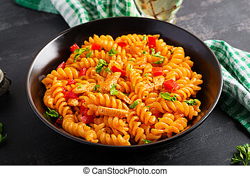 Fusilli pasta with chicken and sweet pepper in tomato sauce. Italian Cuisine.