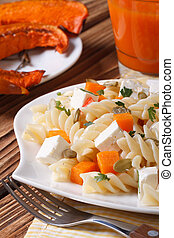 Fusilli pasta with feta and pumpkin on a plate close up. Vertica