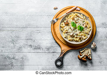 Fusilli pasta with mushrooms in a plate on a cutting Board.