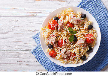 fusilli pasta with tuna, tomatoes and parmesan on the table. horizontal top view