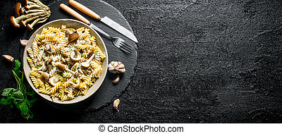 Fusilli paste in plate with mushrooms, garlic and mint leaves.