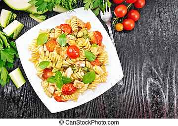Fusilli with chicken and tomatoes in plate on black board top