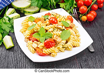 Fusilli with chicken and tomatoes in plate on board