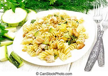 Fusilli with chicken and zucchini in plate on board