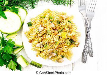 Fusilli with chicken and zucchini in plate on board top