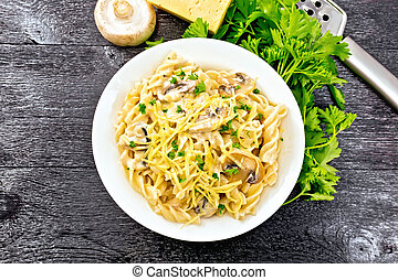 Fusilli with mushrooms in plate on black board top