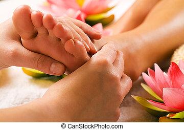 Woman enjoying a feet massage in a spa setting (close up on feet)