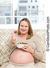 Futur mom with a bowl of strawberries sitting on the sofa