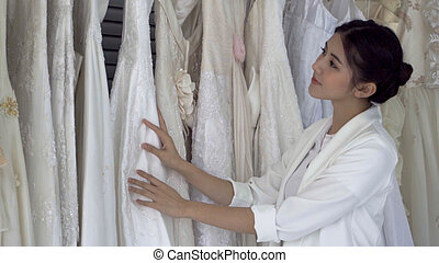 Future bride choosing wedding dress for her upcoming wedding...