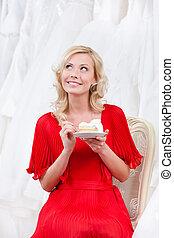 Future bride eats the wedding cake thoughtfully