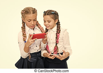 Future is here. Little schoolgirls using smartphones isolated on white. Small kids learning mobile technologies for future life. Future career with digital skills. The future of education, copy space