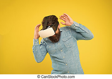 Future of entertainment and communication. Hipster wear VR glasses. Future vision. Bearded man explore VR yellow background. Virtual reality technology and future. Stepping into future