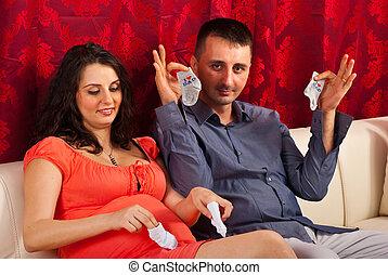 Future parents showing babys cloths