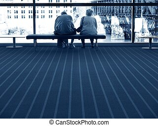 Future - elderly couple sitting on bench together - urban...