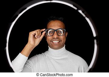 man in glasses over white illumination on black
