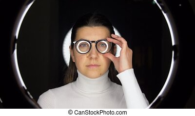 woman in glasses over white illumination on black - future ...