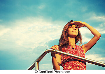 Future - Young woman looking far away in sunset light