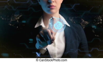Futuristic business woman, uses a hologram of the world...