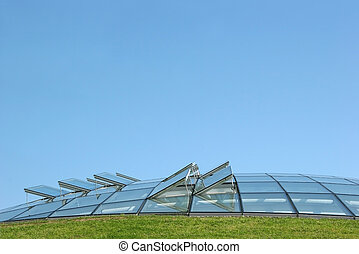 Open glass ventilation windows on a conservatory roof. Set against a blue sky with grass to the foreground.