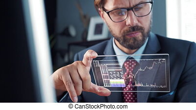 Businessman in suit holds futuristic hologram pad, analyzing trading information