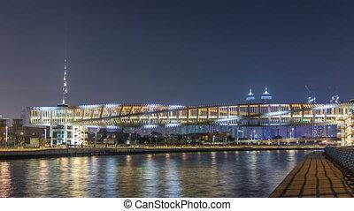 Futuristic Pedestrian Bridge over the Dubai Water Canal Illuminated at Night timelapse, UAE.