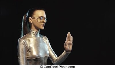 Futuristic woman in silver suit and goggles looking to side...