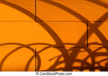 Fuzzy blurry curved shadow on the orange wall. Abstract shadow drawing on the wall in summer at the end day.