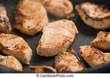 fying turkey fillet slices on nonstick pan, shallow focus