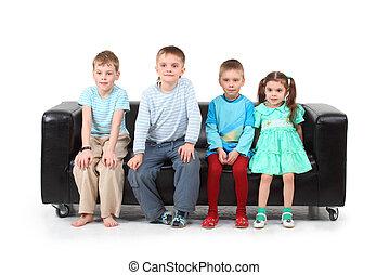 fyra barn, sittande, på, svarta nappa, soffa