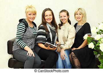 fyra, le, kvinnor, sitta, på, svarta nappa, couch, och, betrakta kamera
