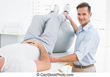fysioterapeut, bistå, man, med, yoga, boll
