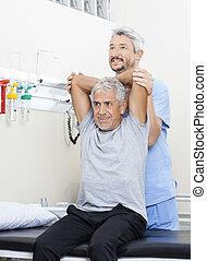 fysioterapeut, bistå, senior mand, ind, exercising, hos, rehab, cent