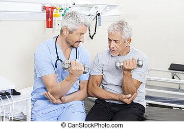 fysioterapeut, bistå, senior mand, ind, ophævelse, dumbbells