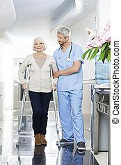 fysioterapeut, hjælper, senior kvinde, hos, det crutches