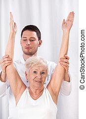 fysiotherapeut, en, oudere vrouw, gedurende, rehabilitatie