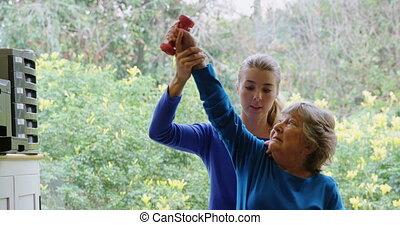 fysiotherapeut, geven, schouder, therapie, met, dumbbell, om te, oude vrouw, 4k
