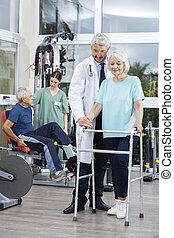 fysiotherapeut, helpen, vrouw met walker, in, fitness midden