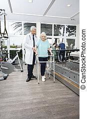 fysiotherapeut, helpen, vrouw met walker, in, rehab, centrum